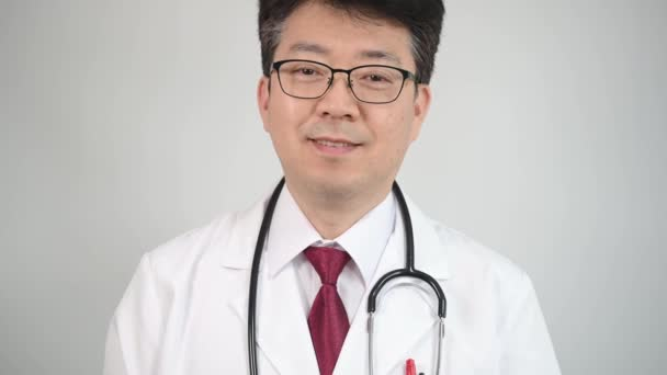 4K. Asian middle-aged male doctor standing with a smile.
