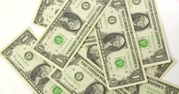 Rotating top view of scattered U.S. dollars against a white background