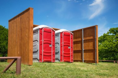 Two red portable restrooms in a park