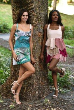 Two models posing in short summer dresses
