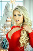 Fotografie Seductive blond young woman with sexy body in red bodysuit posing in the interior with christmas tree on the background.