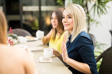 Women sharing some gossip over coffee