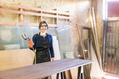 female carpenter with spray gun