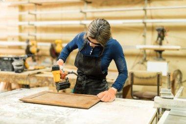 female carpenter using nail gun