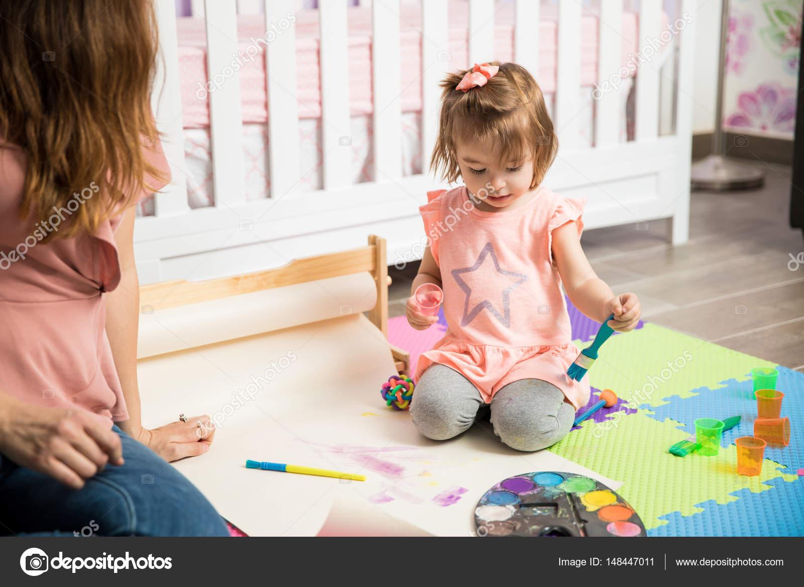 Kind schilderen op de slaapkamer vloer u stockfoto tonodiaz