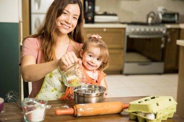 Girl helping mother prepare cake