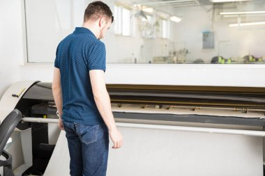 Man printing in a big plotter