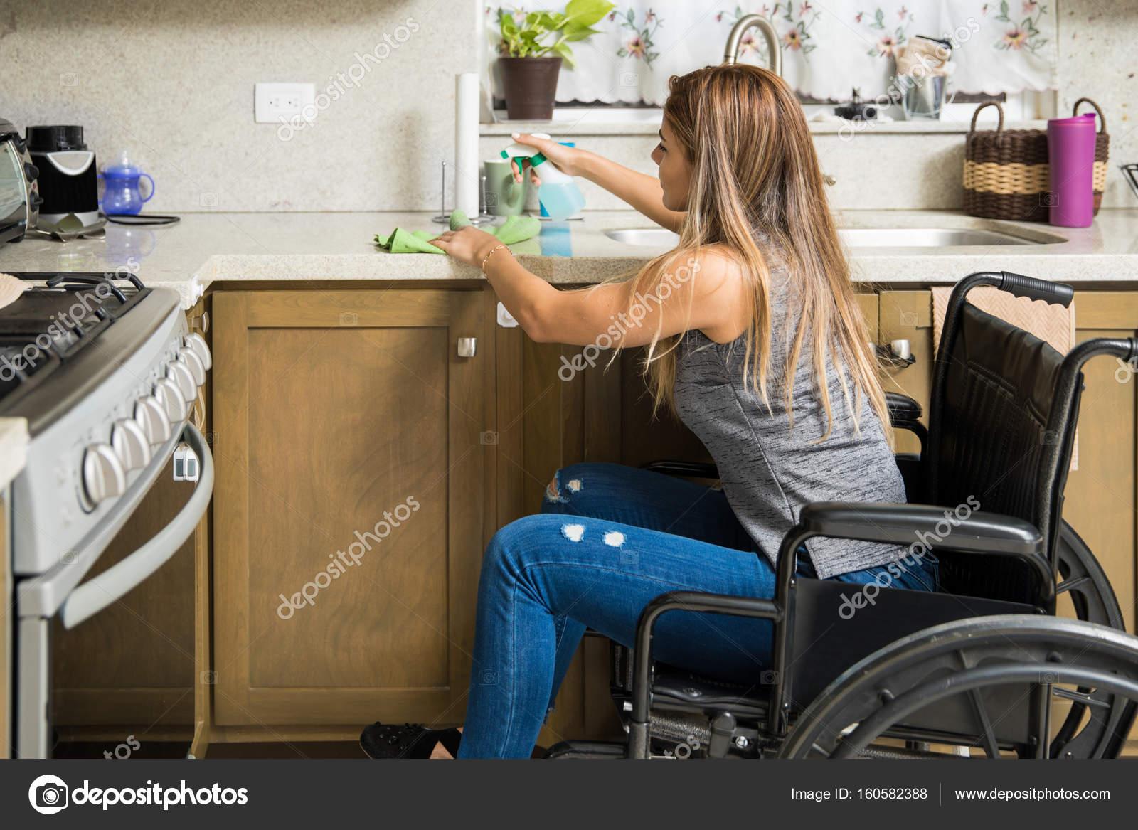Mujer en silla de ruedas limpiar la cocina — Foto de stock ...