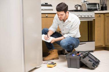 Male technician writing a work report