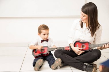 Cute little boy learning how to play the guitar with his kindergarten teacher in school