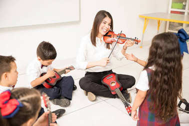Music teacher showing students how to play the violin in a preschool classroom