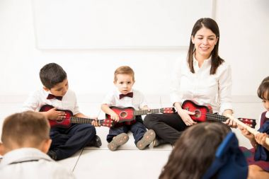 Preschoolers sitting in a circle on the floor playing music instruments next to their teacher in a classroom