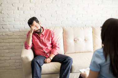 man with depression talking with female counselor