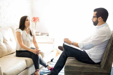 Male psychologist listening to young woman