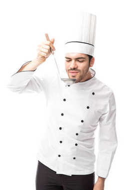Attractive young chef tasting soup