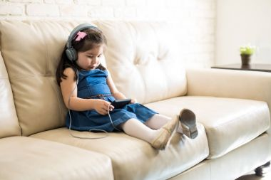 little girl sitting on sofa in headphones and watching movie on smartphone