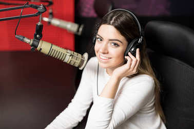 Portrait of young female radio host at radio station with headphones and microphone