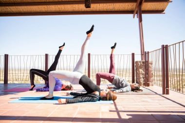 Side view of young women practicing one legged bridge yoga pose in fitness center