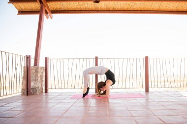 Woman with flexible body bending backwards and doing the scorpion pose during her yoga practice