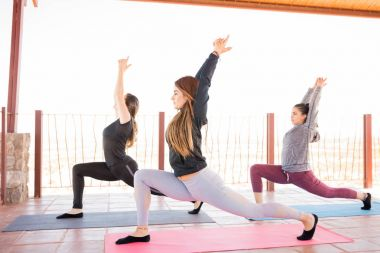 Side view of group of female doing some yoga in yoga class