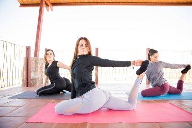 Beautiful young hispanic women doing yoga workout at yoga class, pigeon pose.
