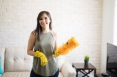 Fotografie Happy cleaning woman holding orange synthetic feather duster