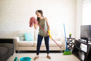 Young woman in protective gloves singing using mop and smiling while cleaning house