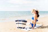 Portrét mladé ženy v bikinách s kloboukem při sezení na plážovém ručníku