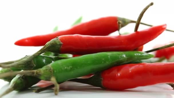 Hrst červené a zelené papriky, pomalu se otáčející na bílý povrch
