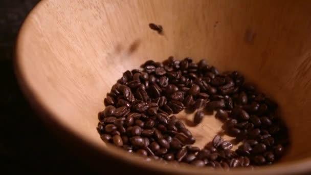 Kaffeebohnen fallen in Holzschale in Zeitlupe