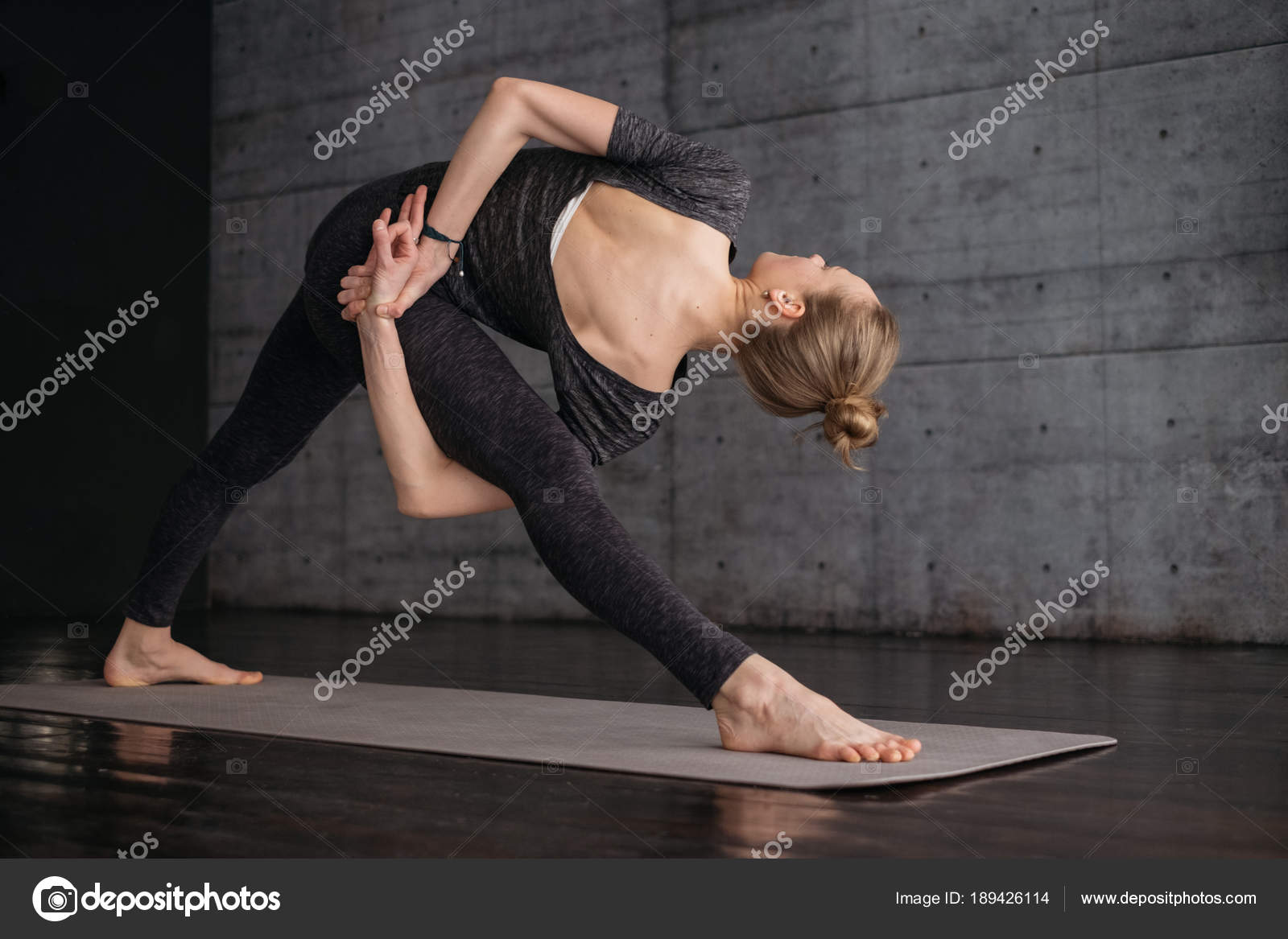 51abf019e5d5 Young Flexible Sporty Woman Extended Triangle Pose Practicing Yoga Grey —  Stock Photo
