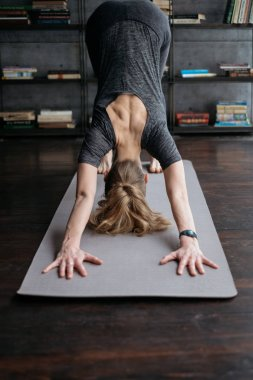 young flexible sporty woman in Downward-Facing Dog, practicing yoga on grey yoga mat on books background