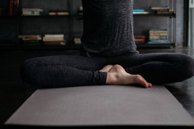 young flexible sporty woman in lotus pose, practicing yoga on grey yoga mat on books background