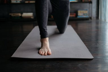 young flexible sporty woman practicing yoga on grey yoga mat on books background