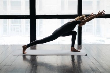 young flexible woman practicing yoga near windows on yoga mat