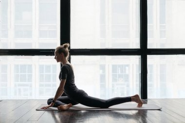 young flexible sporty woman practicing yoga near windows on wooden floor