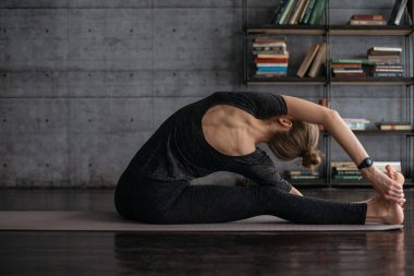 flexible sporty blonde woman practicing yoga on grey yoga mat on books background