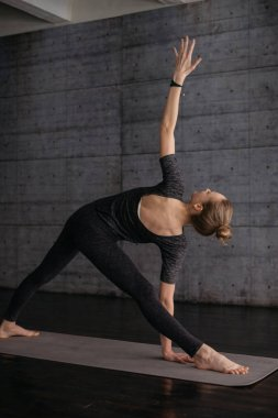 young flexible sporty woman in Extended Triangle Pose, practicing yoga on grey yoga mat on wooden floor