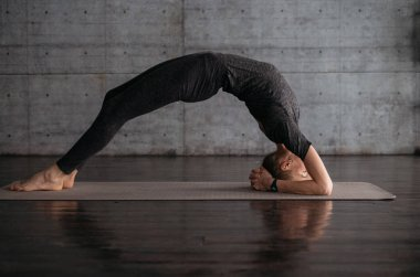 young flexible sporty woman practicing yoga on grey yoga mat on wooden floor