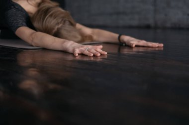 young flexible sporty woman in child pose, practicing yoga on grey yoga mat on wooden floor