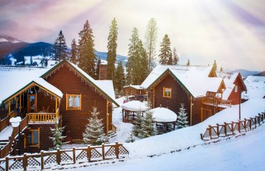 wooden houses surrounded by snow-capped trees
