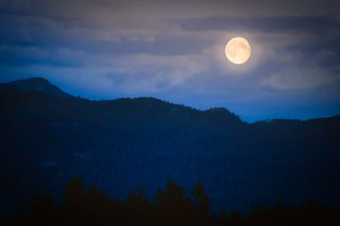 Twilight in mountains with full moon
