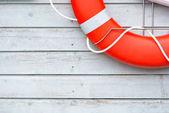 Photo Orange lifebuoy on white wall in port