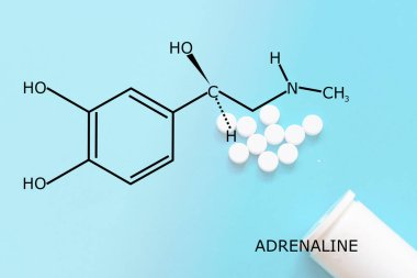 Adrenaline molecule structure with some pills dropped at a blue background.