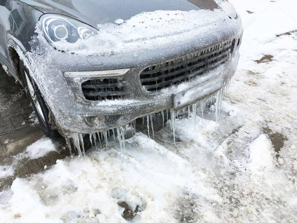 Frozen car in winter season. Luxury sport car parked, covered by ice in winter season.
