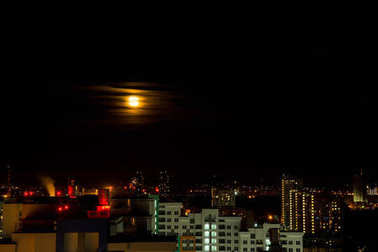 The moon rises above the lights of the night city