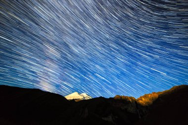 Stars draw fading lines and clouds over Mount Elbrus. Night land