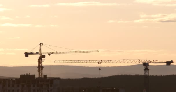 tower cranes at construction site against sunset sky. Ekaterinburg, Russia. Video. UltraHD (4K)