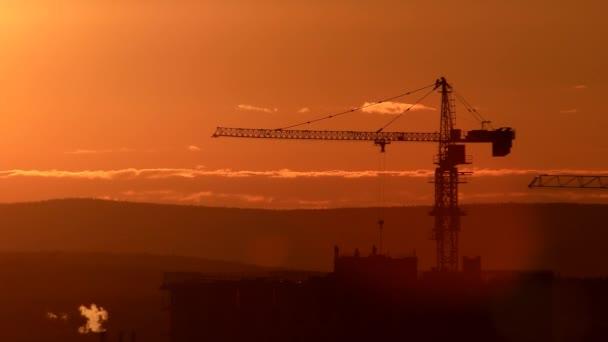 věžový jeřáb na staveništi proti západu slunce na obloze. Jekatěrinburg, Rusko. Video. UltraHD (4k)