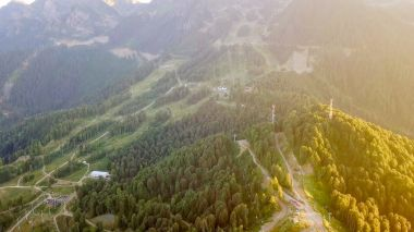 Rosa Khutor plateau, buildings, slopes and chair lifts. Aerial view at sunset